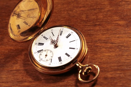 pocketwatch: Antique vintage gold pocket watch closeup on a background of old wood