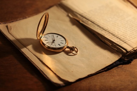 escapement: Antique vintage gold pocket watch closeup on a background of old books Stock Photo