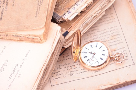 escapement: Antique vintage gold pocket watch closeup on a background of old books, the biblical text and the cover of a book printed before 1914