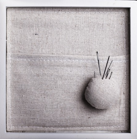 darning needle: Square fabric background with a pillow and needles closeup Stock Photo