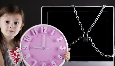 internet safety: Portrait of a young girl near the TV. The TV is closed with a chain lock Stock Photo