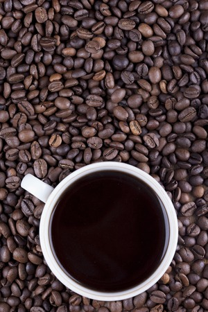 cappuccino cup: Coffee cup and coffee beans on table Stock Photo