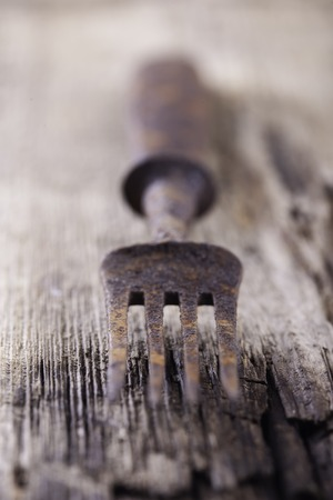 grunge flatware: old rusty fork on a wooden Board close up