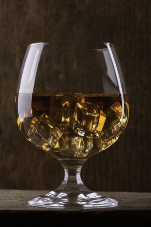 cognac: glass of cognac with ice close up  on cloth background