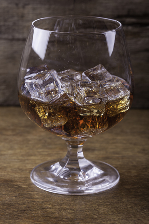 cognac: cognac in a glass with ice close up