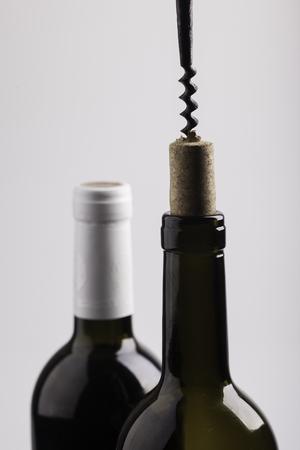 uncork: necks of two wine bottles, cork and corkscrew closeup Stock Photo