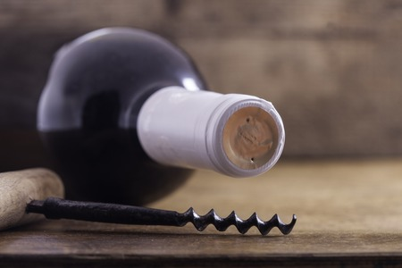 des vins: corkscrew and bottle of wine on the board closeup Stock Photo