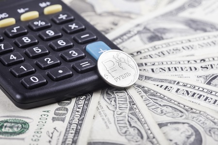 stock exchange: black calculator and coin ruble on the background of American dollars Stock Photo