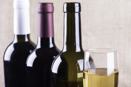 winy: glass of white wine on the background of bottles Stock Photo