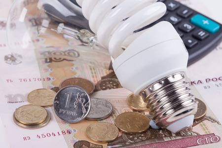 save electricity: Energy saving concept. Electric light bulb with dollar bills, pen and calculator