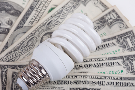 electricity generation: energy saving lamp and dollars close up Stock Photo