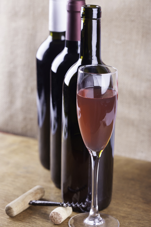 winy: glass of rose wine on the background of bottles