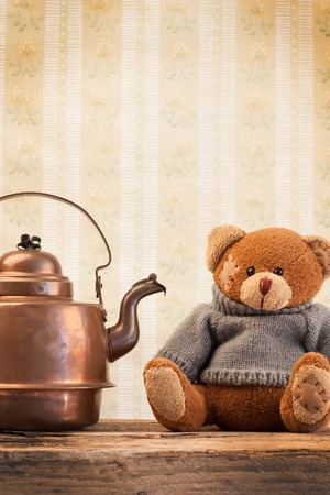 tatty: Teddy bear and vintage copper kettle on the background of old wallpaper Stock Photo