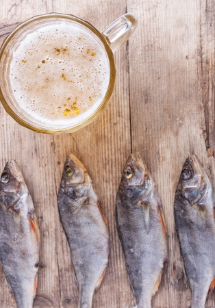 drunkenness: dried fish with beer on the table background