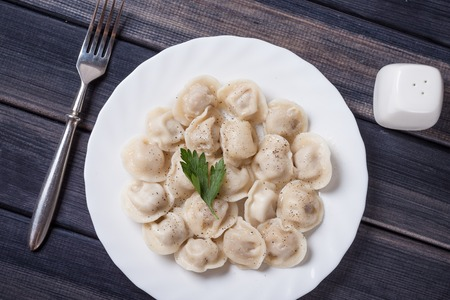 raviolo: plate of hot meat dumplings on the table, top view photo still life Stock Photo
