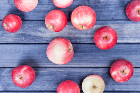 red ripe apples closeup on wooden table background