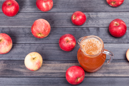 many red apples and juice on wooden table top view background