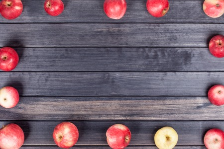 background of red apples on a black wooden table top view