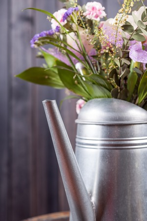 vertical still life flowers in watering can dark background