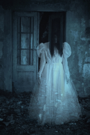 thriller: Spooky woman in a white dress in the field for designer