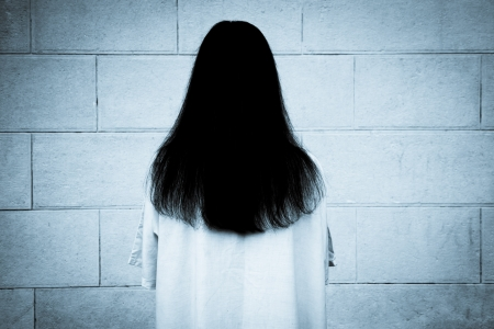 scary girl: woman with long black hair, staring at the wall Stock Photo