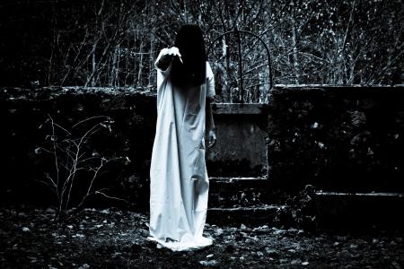 Donna con capelli neri lunghi in abito bianco nella foresta spettrale buio Archivio Fotografico