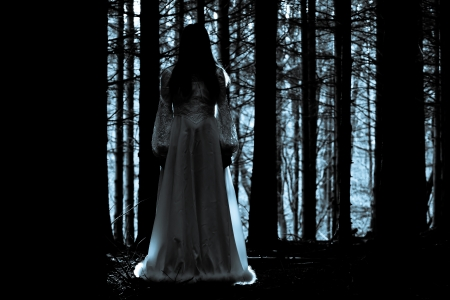 spooky: Woman with long black hair in white dress in the spooky dark forest