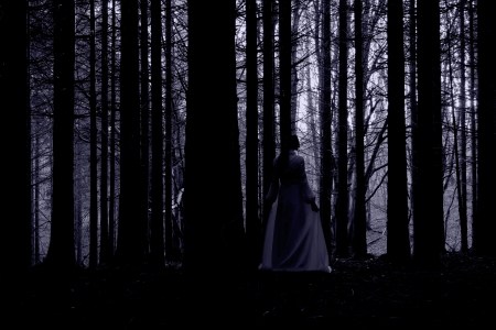 thriller: Woman with long black hair in white dress in the spooky dark forest