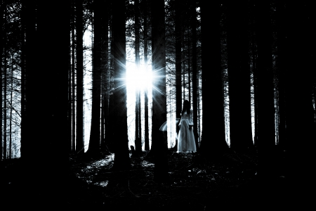 woodland  horror: Woman with long black hair in white dress in the spooky dark forest