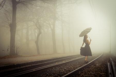 電車の中で黒のドレスと傘を持つ美しい女性のビューの追跡します。