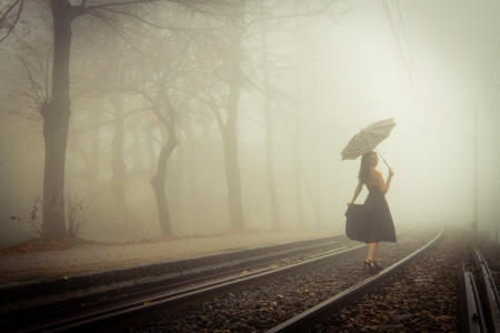 View of a beautiful woman with black dress and umbrella on a train tracks