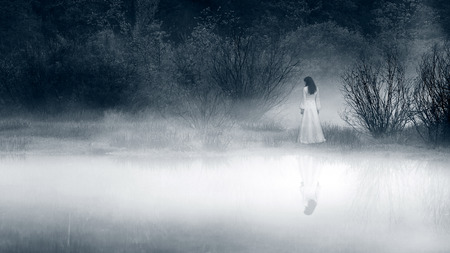 scared woman: Lady at the lake, vintage filter - horror scene