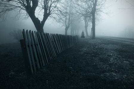 黒のドレスで霧の中で女性のホラー映画のワンシーン。