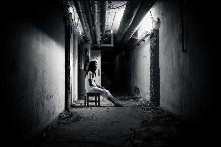 Horror scene of a scary woman in demolished dark hallway