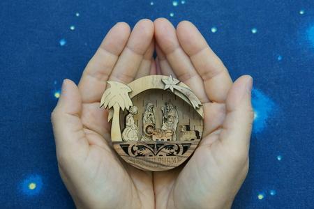 Little nativity scene in the hands on blue sky background