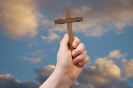 easter cross: Easter religious concept: a child hand sustains a cross on a sky background