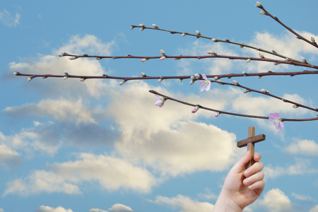Easter background, religious concept. A child hand sustains a cross