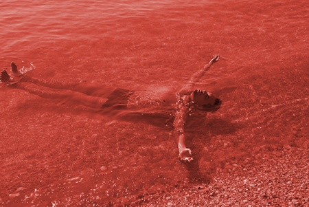 Portrait of young vampire in the bloody sea photo