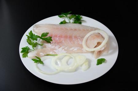 pangasius: Fresh fish  perch, pangasius on white plate black background
