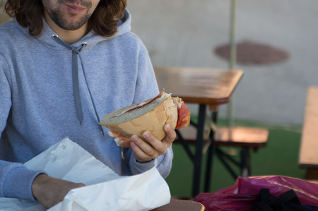 unshaven: young guy with long hair, unshaven eats with appetite big sandwich