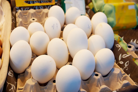 Goose white eggs in the boxes on the tables of the market