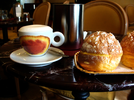 rum baba: White coffee Cup with a gourmet coffee and foam figure