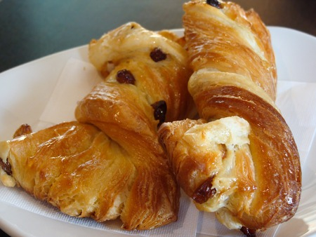danish puff pastry: Sweet pastries, flaky croissants with Golden raisins on a white plate