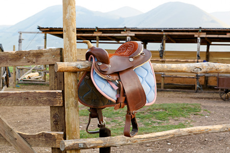 natural materials: Vintage leather saddle made from natural materials and steel stirrups. Meadow, a plateau among the mountains of Italy. Castelluccio.
