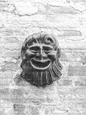 details of architecture, historical buildings of Italy. Stone walls and stone mask. Stock Photo