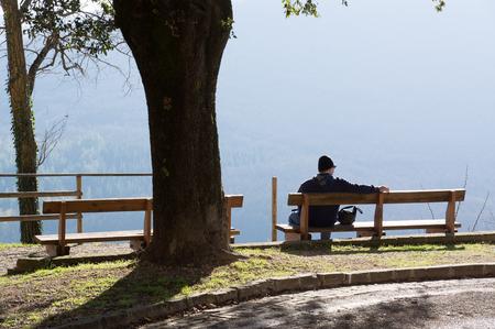 hombre solo: hombre solo que se sienta en banco con la hermosa vista de las montañas. El parque y el bosque fuera de la ciudad.