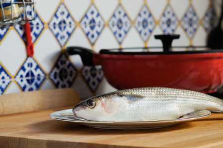 gilt head: Mullet striped mullet contains omega-3 acids, vitamins and minerals. Mullet lying on the plate ready for cooking. A dietary product. Useful to reduce blood pressure. Stock Photo