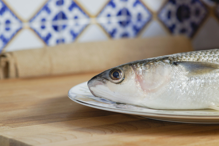 dieta: Mullet striped mullet contains omega-3 acids, vitamins and minerals. Mullet lying on the plate ready for cooking. A dietary product. Useful to reduce blood pressure. Stock Photo