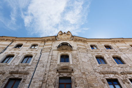 Details of architecture, historical buildings of Italy. Stone walls and stone mask. Ascoli Piceno. Marche. Stock Photo