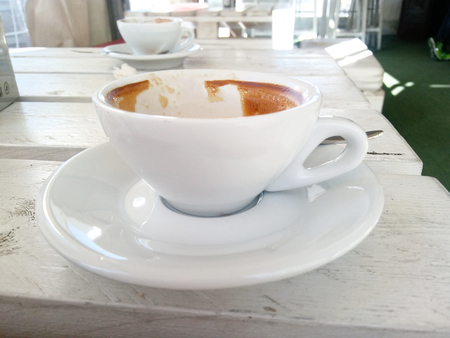 White coffee Cup with a gourmet coffee on the table of the wooden Board cracked